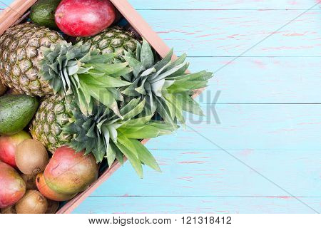 Box Of Tropical Fruits In Box Over Blue Table