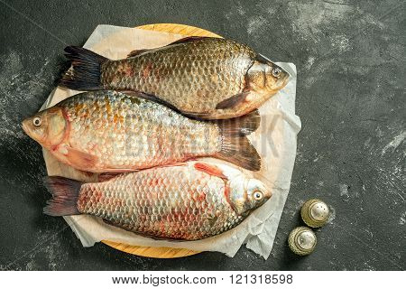 three raw carp fishes lying on wooden cutting board on a dark background with salt and pepper and co