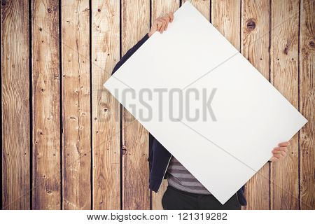 Man holding billboard in front of face against wooden planks background