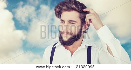 Hipster scratching head while thinking against road leading out to the horizon