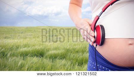 Pregnant woman holding earphones over bump against nature scene