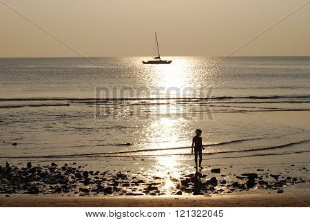 The boy on the beach against the backdrop of yachts and the sunset.