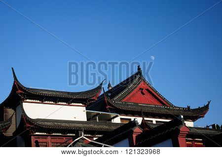 An Asian designed building with waxing moon rising over the roof in Shanghai China.