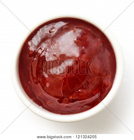 Small white ramekin of red strawberry jam isolated on white. From above.