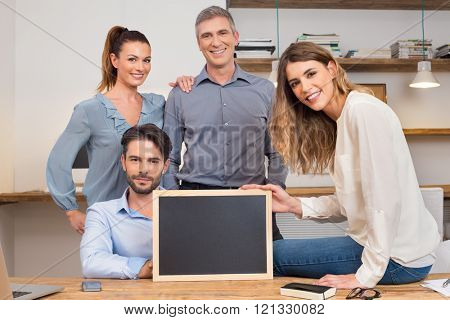 Happy businesspeople in office showing empty blackboard. Leader with his colleagues posing in office. Group of businesspeople holding blank blackboard. Successful business creative team in office.