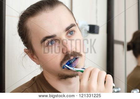 Man cleaning his teeth with blue colour