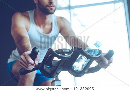 Cycling at gym. Part of low angle view of young man in sportswear cycling at gym