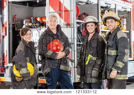 Happy Team Of Firefighters Against Truck
