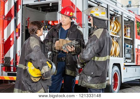 Firefighters Discussing Over Clipboard Against Truck