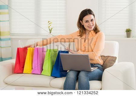 Woman Sitting On Sofa With Laptop And Shopping Bags