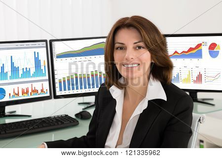 Businesswoman With Graphs On Multiple Computers
