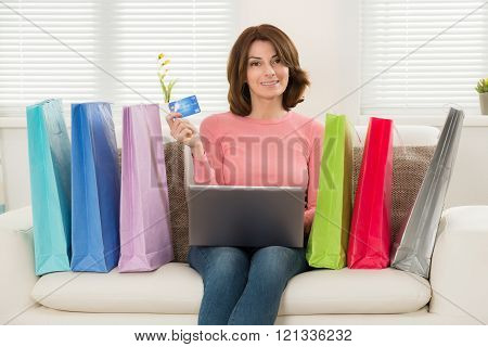 Woman Using Card While Shopping On Laptop