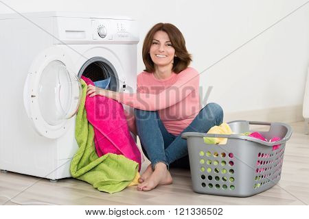 Happy Woman Putting Clothes Into Washing Machine