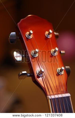 Red acoustic guitar headstock under colourful bright light