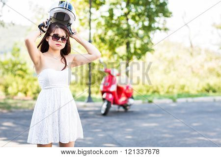 Portrait Of Happy Young Woman With Helmet In Hands Near Red Scooter. Defocused Background.
