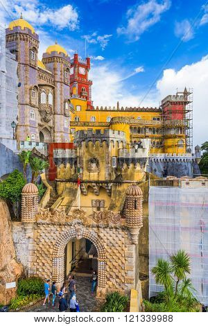 SINTRA, PORTUGAL - OCTOBER 18, 2014: Tourists walk under scaffolded structures at Pena National Palace.