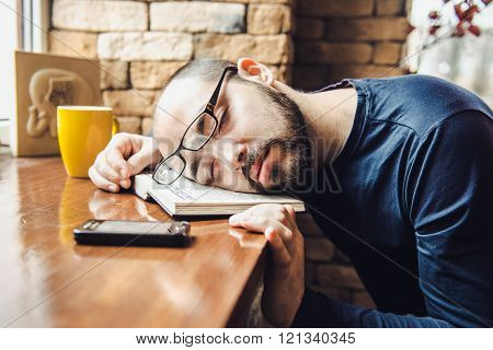 unshaven man in glasses tired, fell asleep on a table in a cafe