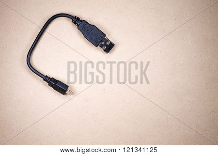 Usb plug isolated over wodden background. usb cable