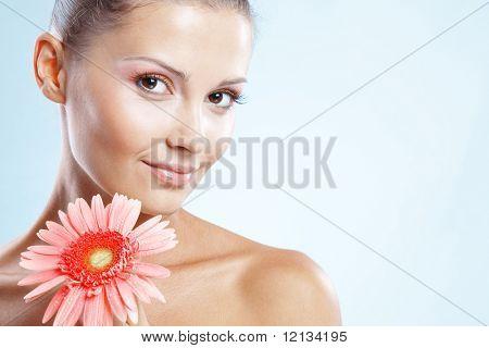 Mooie vrouw met verse make-up en heldere huid bedrijf roze daisy over blauwe studio shot