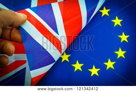 UK versus European Union concept with hand turning flag