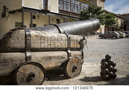 Ancient cannon on wooden wheels and iron cannonballs