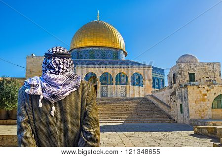 JERUSALEM ISRAEL - FEBRUARY 16 2016: The pensive Palestinian in keffiyeh stands next to the staircase leading to the Dome of the Rock on the Temple Mount on February 16 in Jerusalem.