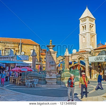 JERUSALEM ISRAEL - FEBRUARY 16 2016: The beautiful Muristan Square full of noisy merchants and tourists with the stone bell tower of the Lutheran Kirche of the Redeemer on the background on February 16 in Jerusalem.