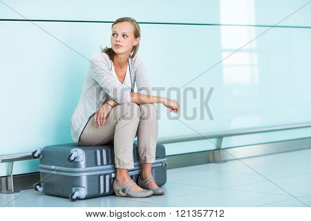 Young, female frustrated passenger at the airport, waiting desperately for her delayed flight (color toned image; shallow DOF)
