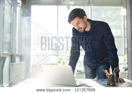 Handsome male worker is using a notebook