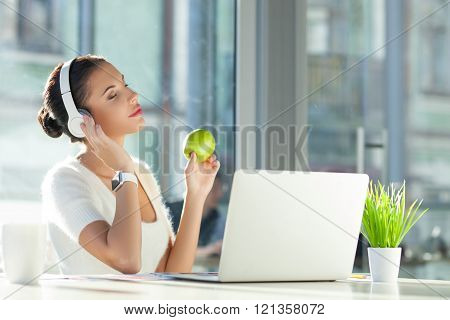 Cheerful female worker is relaxing at work
