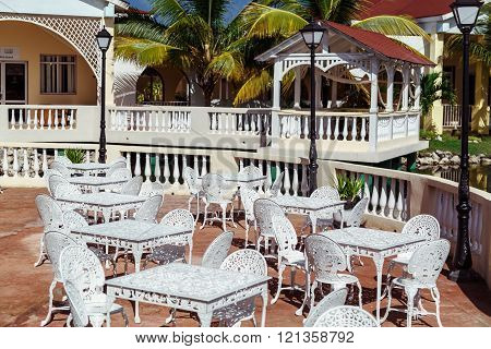Gorgeous inviting view of Memories resort landscape, outdoor cafe, patio with vintage retro chairs