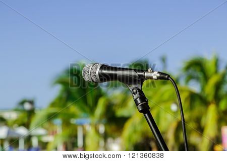 Nice view of microphone on stand in outdoor tropical garden against blue sky background