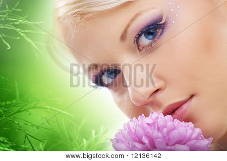 Cheerful young cute woman face with flower over natural green background