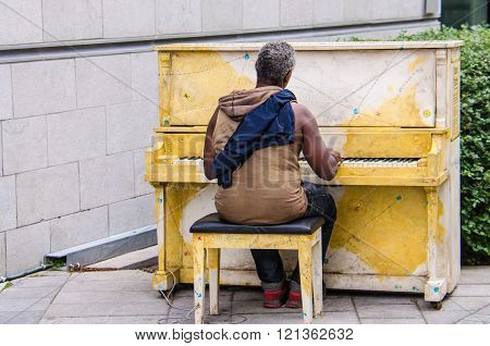 July 26, 2014 - Montreal, Canada: Homeless man playing a piano on a street in Montreal, Quebec, Cana
