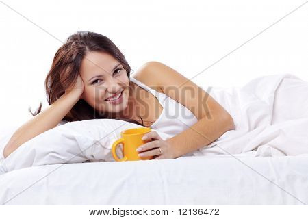 Studio portrait of young beautiful woman ob bed