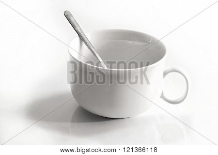 White Cup And A Steel Teaspoon
