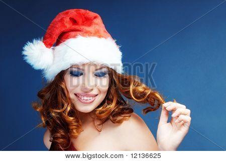 Cute happy Santa helper girl posing on blue studio background