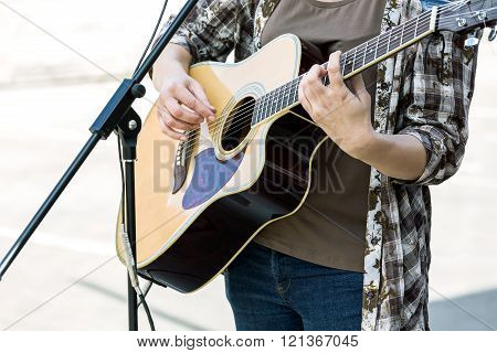 woman playing on acoustic guitar outdoor