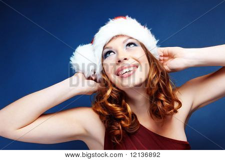 Cute happy Santa helper girl posing on blue studio background