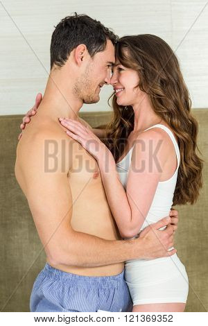 Romantic couple looking at each other and embracing on bed