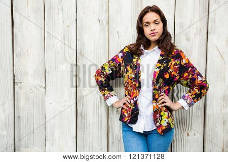 Hipster woman posing with hands on hips on wooden background