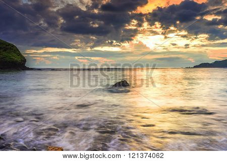 Natural beach stone and wave with orange skies background