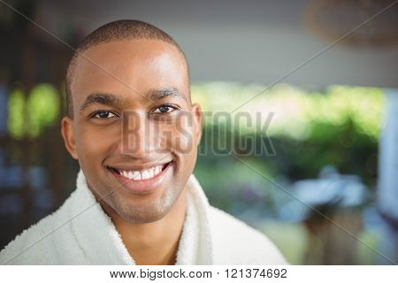 Smiling man in bath robe drinking coffee at home