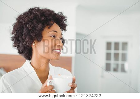 Pretty woman in bath robe drinking coffee in the kitchen at home