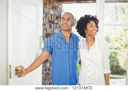 Happy couple about to open the door of their house