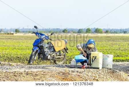 TANJUNG KARANG MALAYSIA - 31 JANUARY 2016 : Unidentified farmer preparing insecticide with traditional way on a paddy field in Tanjung Karang Malaysia. Selective focus and shallow DOF?
