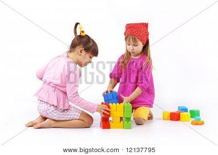 Retrato de dos niños con constructor sobre blanco