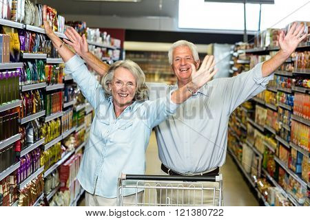 Happy senior couple at the supermarket raising arms