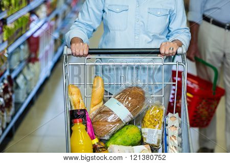 Mid section of smiling senior woman pushing cart at the supermarket