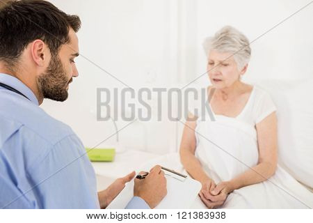 Home nurse listening to elderly woman and writing on clipboard in the bedroom